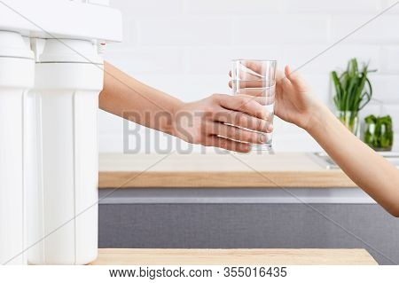 Womans Hand Gives A Glass Of Purified Water To Her Child. Concept Purification Of Water By Osmosis F