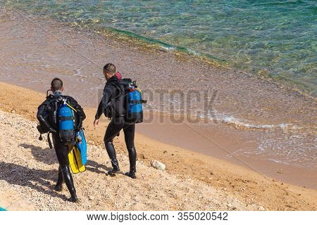 Tossa De Mar, Spain - August 4, 2019: Two Unknown Divers In Wetsuits And Scuba Divers On A Sandy Bea