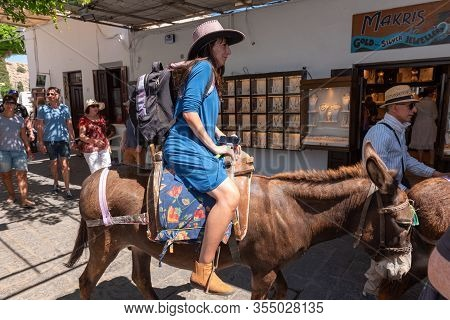 Rhodes, Greece - May 14, 2018: Woman Riding Donkey. Using Donkey Taxi To The Acropolis Is A Popular
