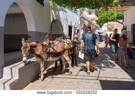 Rhodes, Greece - May 14, 2018: Main Parking For Donkeys In Lindos. Using Donkey Taxi To The Acropoli
