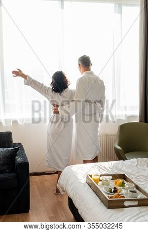 Back View Of Boyfriend And Girlfriend In Bathrobes Hugging And Looking Trough Window In Hotel