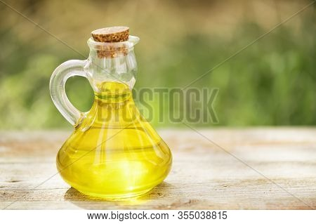 Glass Bottle Full Of Golden Vegetable Oil On A Wooden Table On A Green Blurred Background. Mock Up F