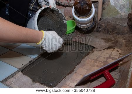 Laying Cement On The Floor. Fill The Floor. Mans Work. Masters Hand. Liquid Cement. A Mans Hand Leve