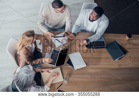 Overhead View Of Multicultural Colleagues Talking And Sitting At Table During Meeting