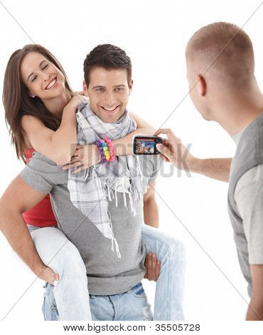 Friends having fun, taking photo of trendy young couple, laughing, cutout on white.