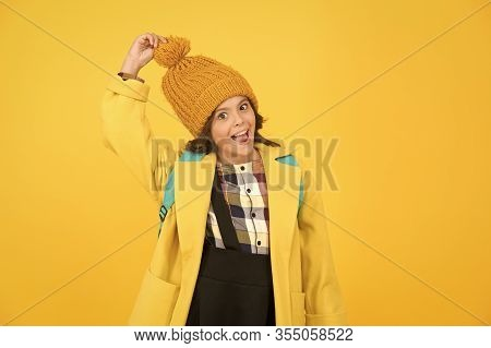 Warm And Stylish. Happy Small Schoolgirl Touch Stylish Pompom Hat. Little Child Smile With Stylish A