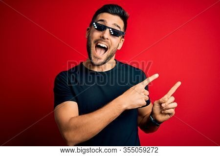Young handsome man wearing funny thug life sunglasses over isolated red background smiling and looking at the camera pointing with two hands and fingers to the side.
