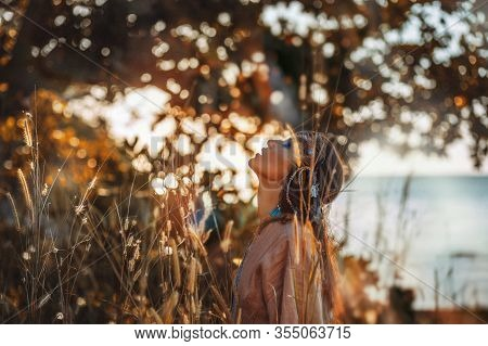Beautiful Young Stylish Woman On The Field At Sunset. Oriental Tribal Princess