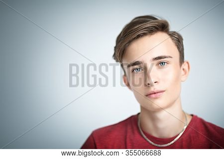 A portrait of a young goodlooking guy in a red t-shirt. Beauty of men, casual fashion.