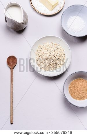 Ingredients For Oat Porridge: Rolled Oats Or Flakes, Sugar, Salt, Milk And Butter In A Bowls On Grey