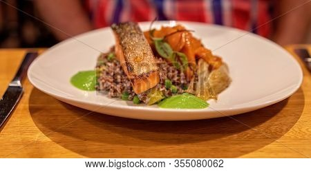 A Delicious Barramundi Fish Dish With Vegetables Served In A Restaurant