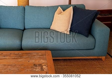 A Lounge Settee With Cushions And A Table All Set On A Hessian Rug