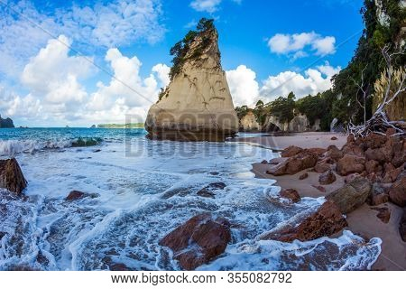 Tidal wave in Cathedral Cove. Sunset. Huge boulders and picturesque rocks on a sandy beach. The New Zealand, North Island. The concept of exotic, ecological and photo tourism