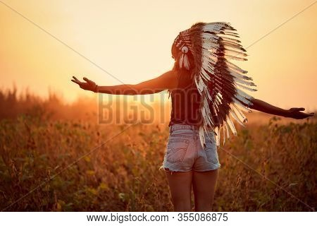 Beautiful American Indian girl at field in countryside at sunset.