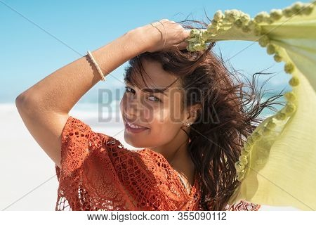 Smiling fashion woman holding green scarf over head while walking at beach. Happy active and healthy woman enjoying summer vacation. Tanned girl in red crochet running at sea and looking at camera.