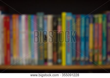 Blurred Background With Colorful Books: University Or College Textbooks And Fiction. Bookshelf At Ho