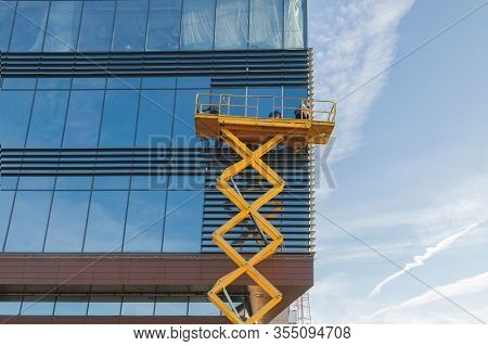 Workers Are Repairing The Glazing In The Office Building. Scissor Lift Platform.