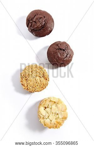 Chocolate cupcakes, cookie with almond flakes and sesame cookies isolated on white background. Set of desserts with almond cracker, brown cupcakes and crispy sesam cake cut out