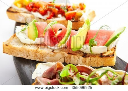 Bruschetta with tuna and avocado closeup view. Delicious antipasto with seafood. Tasty italian snacks with baked baguette. Starter dish with greenery and cheese. Restaurant food composition