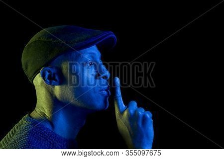 Black Man With Blue And Yellow Light, With Finger On Lips Making Silence Gesture, Wearing A Flat Cap