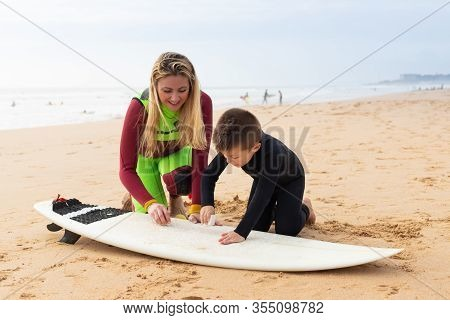 Mother And Son Waxing Surfboard On Sea Coast. Cheerful Mother And Little Son In Wetsuits Sitting On