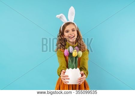 Image of a cute optimistic positive cheery young girl child in easter holiday bunny ears isolated over blue wall background.