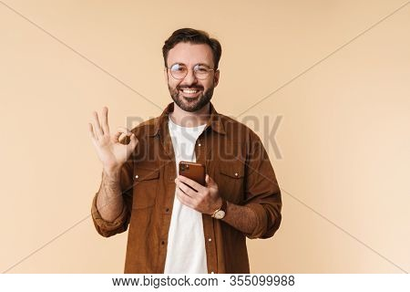 Portrait of a cheerful young arttractive bearded man wearing casual clothes standing isolated over beige background, using mobile phone, ok gesture, ok