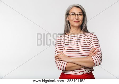 Image of adult mature woman with long gray hair wearing eyeglasses looking at camera isolated over white background