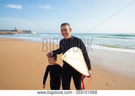 Happy Father And Son With Surfboard. Cheerful Middle Aged Father Holding Surfboard And Walking With