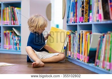 Child In School Library. Kids Reading Books.