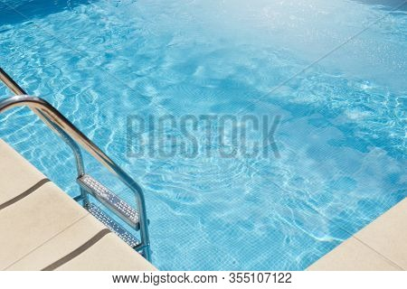 Top View Of Swimming Pool With Clear Blue Water, Metal Stairs Into Pool, No People Inside, Transpare