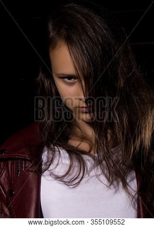 Beautyful Girl In Leather Jacket In A Dark. Mysterious Disobedient Child, Problems With Early Growin