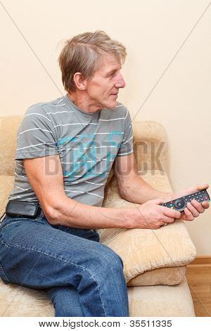 Senior Man With Remote Control Sitting On Couch And Looking At Tv Set