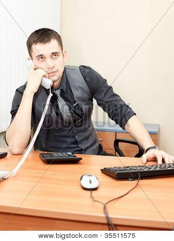 Smart Businessman Speaking On Phone While Working On Desktop Computer