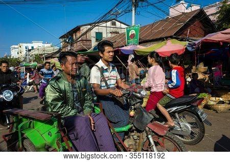 Mandalay, Myanmar - January 12, 2020: Man driving sidecar motorbike with passenger at Zay Cho Market