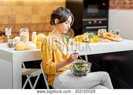 Young And Cheerful Woman Eating Salad At The Table Full Of Healthy Raw Vegetables And Fruits On The