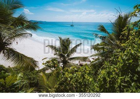 Holiday Vacation At Petite Anse Paradise Beach Framed By Green Foliage. La Digue Island, Seychelles