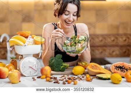 Sports Woman Eating Salad, Standing With Lots Of Healthy Fresh Food On The Kitchen. Concept Of Losin