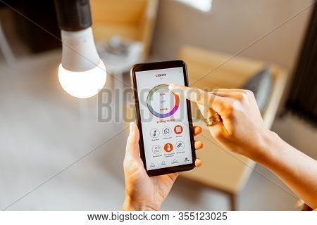 Controlling Light Bulb Temperature And Intensity With A Smartphone Application. Concept Of A Smart H