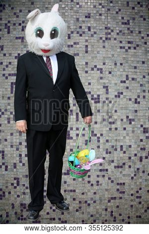 Easter Bunny. Easter Bunny in a Business Suit. Easter Bunny with a Colored Tile Background. Easter Bunny Man in a suit brings a basket of goodies for Holiday Fun to all. Man with a Rabbit Head.