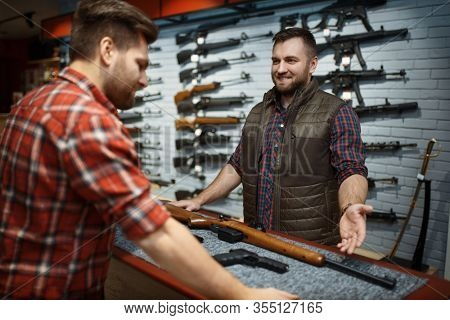 Man and owner choosing rifle in gun shop