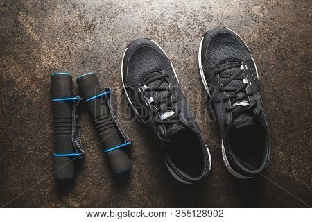 Fitness concept. Black sports shoes and dumbbells. Top view.