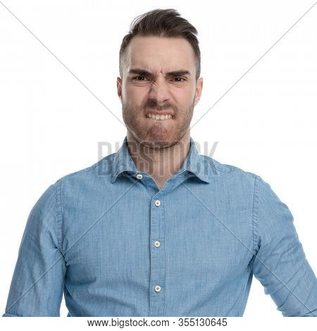 Bothered casual man biting his lips and frowning while wearing blue shirt, standing on white studio background