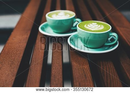 Two Cups Of Cappuccino With Latte Art On Wooden Background. Beautiful Foam, Greenery Ceramic Cups, S