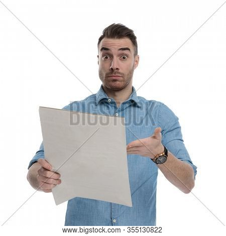 Bothered casual man reading and pointing at newspaper while wearing blue shirt, standing on white studio background
