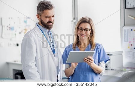 A Dentist With Dental Assistant In Modern Dental Surgery, Working.