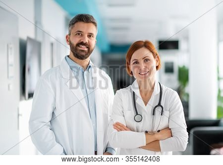 A Portrait Of Man And Woman Doctor Standing In Hospital.