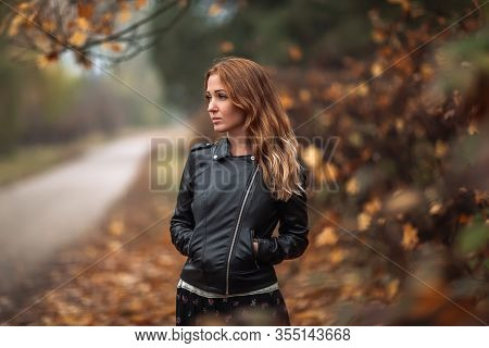 Fabulous Redhead Dreamy Woman With Long Curly Hair On Blurred Autumn Background. Girl On Fabulous Ba