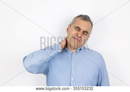 Adult Handsome Man With Grey Hair Wearing Blue Shirt Touching His Neck With Hand Suffering From Sudd
