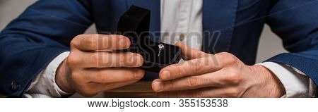 Cropped View Of Jewelry Appraiser Holding Box With Jewelry Ring At Table Isolated On Grey, Panoramic